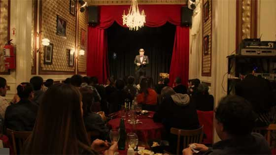 Man on stage performing under chandelier with full audience seated at tables