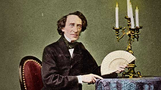 The great Hofzinser facing the camera sitting at a table with candles holding a fan