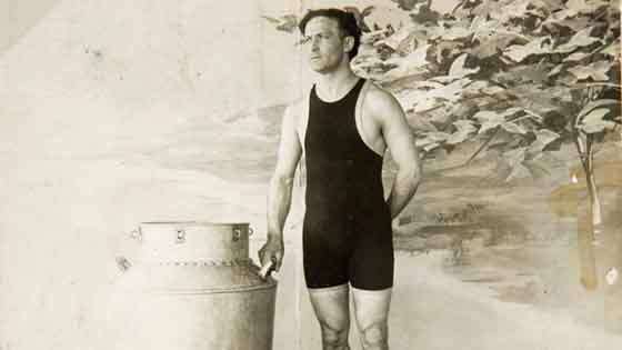 Promo photo of Houdini wearing swimsuit next to his Milk Can Escape