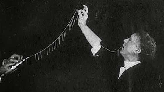 Black and white photo of houdini holding string of needles from his mouth
