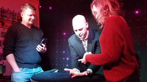 Max wearing a red jacket on stage performs sleight of hand with playing cards for two guests next to him