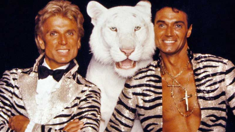 Magicians Siegfried and Roy with white tiger standing between them