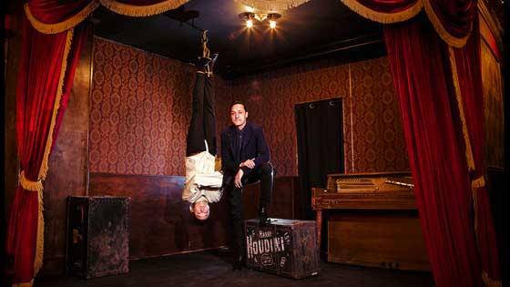 Black Rabbit Rose Theatre with a man in a straight jacket hanging upside-down from the ceiling