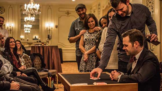 Dennis Watkins performs an intimate style of magic with playing cards and audience members touching the table