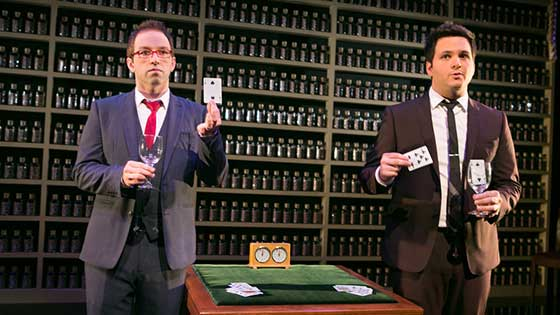 Derek and Helder in Nothing to Hide, each hold a playing card and a wine glass in unison