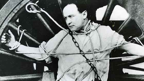 Houdini tied with ropes and leather straps to a large train wheel