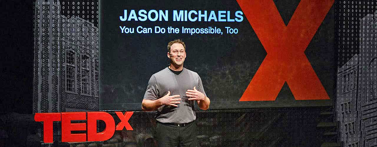Jason Michaels speaking while on stage at a TedX conference