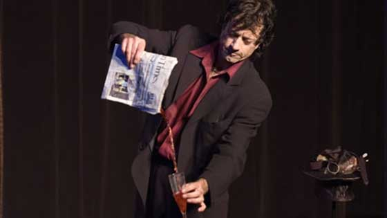 Rocco pouring liquid from a newspaper at Monday Night Magic