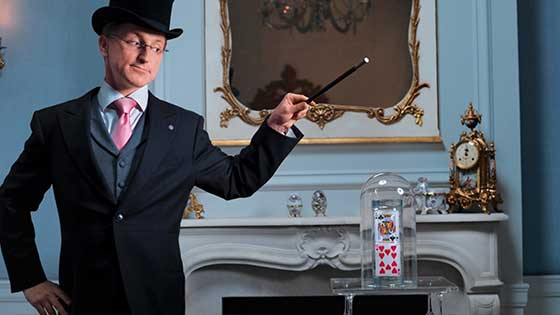Wearing a tuxedo and top hat, Steve Cohen whirls his magic wand
